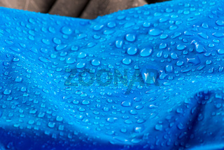 Nylon waterproof fabric with blurred foreground and background. Rain Drops on Water Resistant Textile waterproof coating background with water drops
