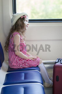 Little fashionable girl sitting on armchair near the window in the train