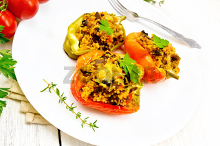 Pepper stuffed with mushrooms and couscous in plate on board