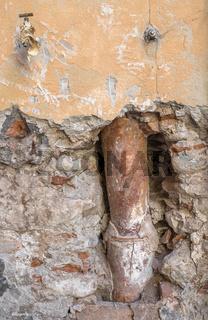 Old gutter inside the broken wall