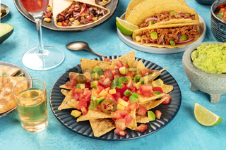 Mexican food with nachos in front and taco shells with pulled pork, burritos, guacamole and other dishes, with tequila and lime on a blue background