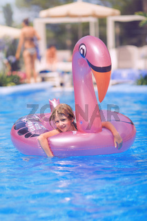 Young girl playing with rose plastic flamingo in swimming pool