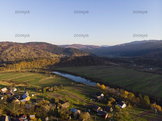 Carpathian Mountains, Ukraine. Aerial Drone View of autumn mountains with forests and river, meadows