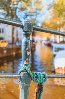 Selective focus of green post and rope in front of dreamy canal in Amsterdam in golden autumn light