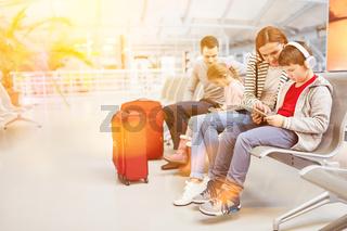 Familie mit Kindern beim Warten am Flughafen