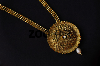 Artificial golden necklace on a black background.