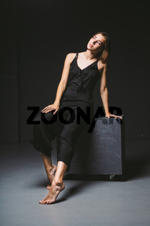 Young Caucasian female model posing in studio black background.Girl sitting in a black dress on a dark wall. Subject severe poor psychological state, intra, problems, personality conflict