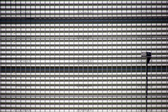 Grid fence in front of corrugated iron