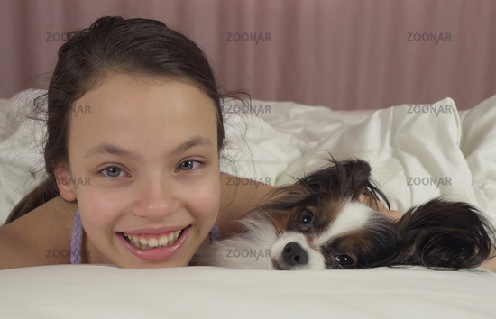 Happy teen girl kisses and plays with dog Papillon in bed