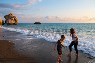 A boy and a girl play barefooted at the beach againt the Petra tou Romiou rocks bathed in afternoon light, in Paphos, Cyprus.