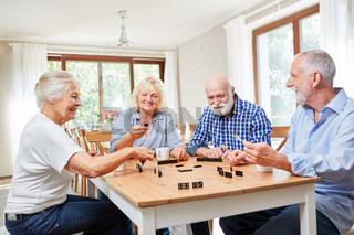 Senioren als Freunde spielen zusammen Domino