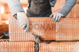 Details of male worker, bricklayer. Professional worker building house with rubber hammer and bricks