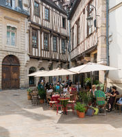 picturesque French outdoor cafe in the historic old town of Dijon with half-timbered houses behind