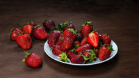 Fresh strawberries in ceramic bowl on dark wooden background.