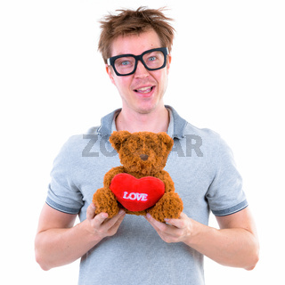 Funny young nerd man with big eyeglasses holding teddy bear