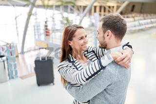 Glückliches Paar im Flughafen Terminal umarmt sich