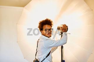 Junger Fotograf mit Studioleuchte und Blitzlicht