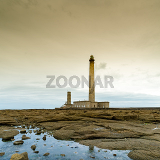 tall stone lighthouse with rocky shore tidal pools in foreground under a stormy sky