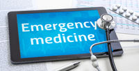 The word Emergency medicine on the display of a tablet
