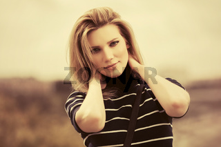 Young fashion blond woman in striped turtleneck t-shirt walking outdoor