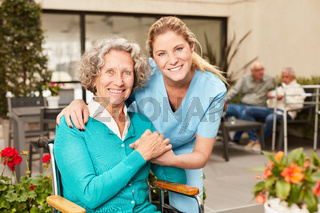 Glückliche Senior Frau und Pflegehilfe