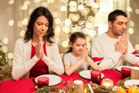 family praying before meal at christmas dinner