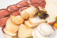 Assortment of cheeses and slices of cured pork loin.