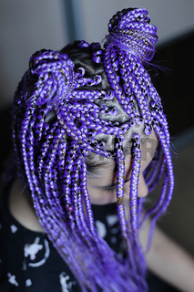 purple braids on the head of the girl, colored hair, youth hairdo close-up, thick boxer braids
