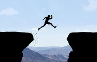 Man jumping over abyss in front of mountain background.