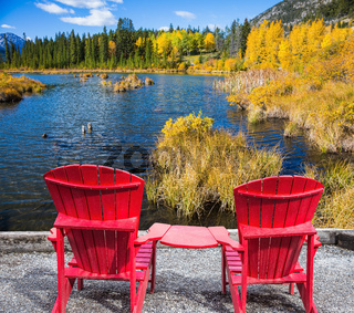 Two red deck chairs on the lake