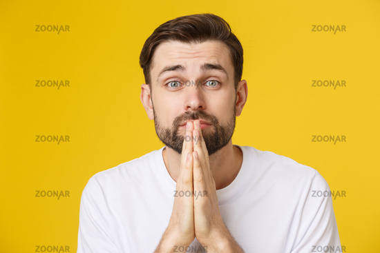 Young guy dressed casually isolated on yellow background, having put hands together in prayer or meditation, looking relaxed and calm.