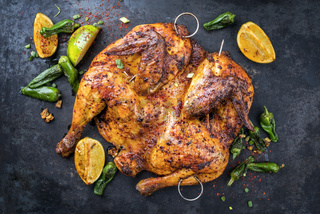 Spatchcocked barbecue chicken al mattone with vegetable as top view on an old board