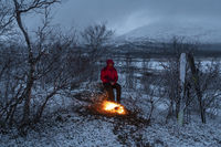 Man beside a campfire in the mountains, Lapland, Sweden