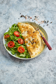 Classic egg omelette served with cherry tomato and arugula salad on side