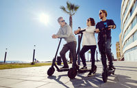 Three best friends young 20s -30s girl and guys spend time outdoors gathered together driving on electric scooter modern land vehicle, easy comfort usage, technology urban transportation concept image