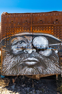 Bolivia Uyuni face of man with beard drawn on old locomotive