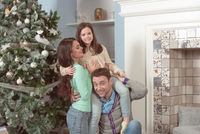Family hug near Christmas tree