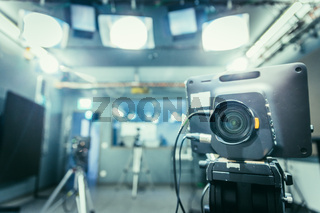 Film camera in broadcasting studio, spotlights and other equipment