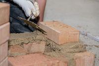 Mason builds brick wall - closeup craftsman