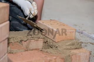 Maurer errichtet Ziegelwand - Nahaufnahme Handwerker