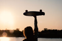 Silhouetted Woman posing with her hands holding skateboard raised up in the sunset sky