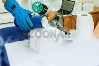 Valencia, Spain - May 25, 2019: Pouring liquid nitrogen with protective glove.