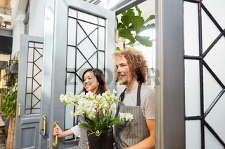 Glückliches Floristen Team mit Blume als Geschenk
