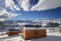 Small wooden houses at snowy winter mountains and blue sky with clouds