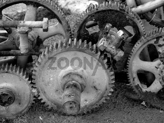 monochrome image of old rusting cogwheels with broken teeth and bolts