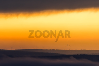 The sun rises over the wind power wheels