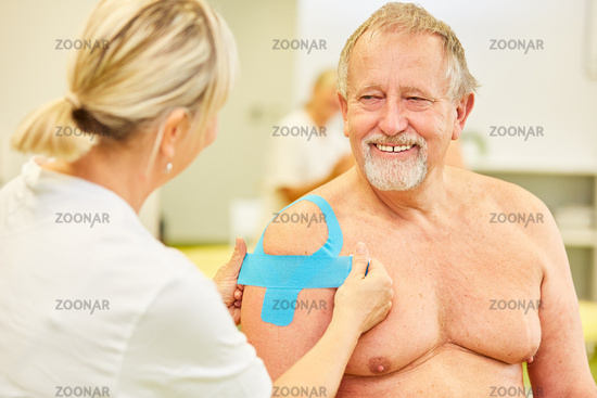 Senior Mann mit blauem Kinesio Tape an der Schulter