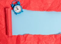 Ripped cardboard with a mini alarm clock placed above a soft colour table. Thick torn paper on a pastel plain backdrop. Artistic way of arranging flat lays photography