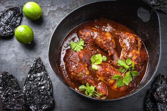 Traditional roasted Mexican pollo adobado chicken haunch with guajillo and hot ancho chilis as closeup in a modern design cast iron stewpot