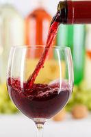 Wein einschenken eingießen aus Weinflasche Hochformat Weinglas Rotwein Flasche
